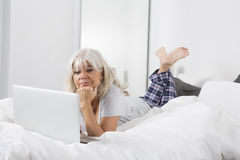 Mitt- ålderkvinna med en bärbar dator i säng Arkivbild