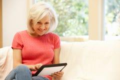 Mitt- ålderkvinna som hemma använder minnestavlan arkivbild