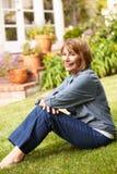 Mitt- ålderkvinna som kopplar av i trädgård fotografering för bildbyråer