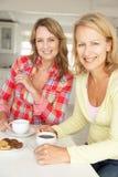 Mitt- ålderkvinnor som pratar över kaffe Arkivbild