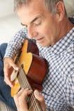 Mitt- ålderman som leker den akustiska gitarren Royaltyfria Foton