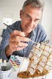 Mitt- ålderman som målar en model ship hemmastadd arkivbild