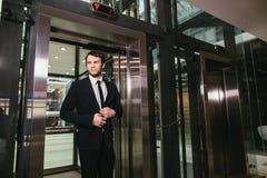 Mitt åldrades affärsmannen med portföljen som var kommande ut från hissen arkivbilder