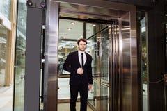 Mitt åldrades affärsmannen med portföljen som var kommande ut från hissen Arkivbild