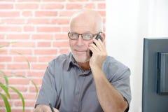 Mitt åldrades affärsmannen Sitting på skrivbordet, med telefonen royaltyfri fotografi