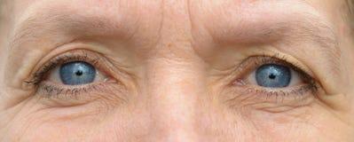 Mitt åldrades caucasian kvinnaögon i närbild arkivfoto