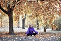 Mitt åldrades caucasian kvinnan sitter under det stora trädet på hösten parkerar bara i meditation poserar med stängda ögon Tillf royaltyfria bilder