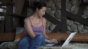 Mitt åldrades den asiatiska kvinnan som hemma skriver på bärbara datorn, långsam mo lager videofilmer
