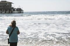 Mitt åldrades höga kvinnan i hennes 60-tal promenerar shorelinen i Santa Monica California royaltyfri bild
