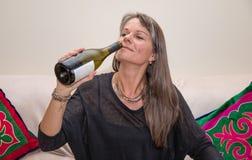 Mitt åldrades kvinnan med en flaska av vitt vin Arkivbilder