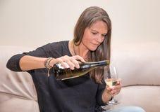 Mitt åldrades kvinnan med en flaska av vitt vin Arkivbild