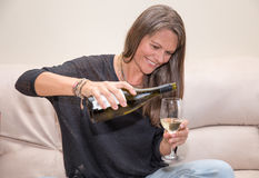 Mitt åldrades kvinnan med en flaska av vitt vin Arkivfoton