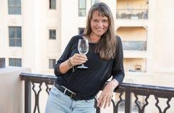 Mitt åldrades kvinnan på en balkong med ett exponeringsglas av vitt vin Royaltyfri Foto