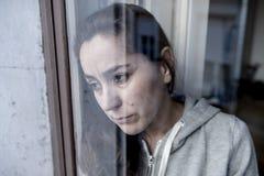 Mitt åldrades latinskt ledset och deprimerat se för kvinna till och med fönsterförfriskningen i fördjupningsbegrepp royaltyfria foton