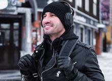 Mitt åldrades le mannen som går vid gatan i vintertid och lyssnar till musiken via hörlurar Arkivbild