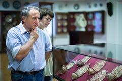 Mitt åldrades män, och kvinnasamlaren utvärderar utställningen i historiskt museum royaltyfri foto