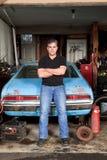 Mitt åldrades mananseende och benägenhet mot hans gamla bil i hans garage Royaltyfria Foton