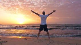 Mitt åldrades mannen gick upp och hälsar solen på kusten med härlig soluppgång lager videofilmer