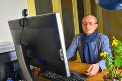 Mitt åldrades mannen med exponeringsglas som sitter på skrivbordet Mogen man som använder persondatorn Högt begrepp home manworki arkivfoto