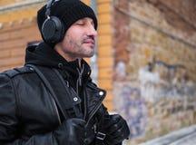 Mitt åldrades mannen som går vid gatan i vintertid och lyssnar till musiken via hörlurar Arkivfoto