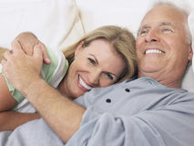 Mitt åldrades par som omfamnar i säng arkivfoton