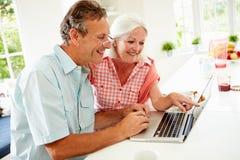 Mitt åldrades par som ser bärbara datorn över frukosten Arkivbild