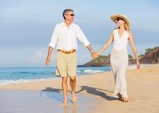 Mitt åldrades par som tycker om, går på stranden Arkivbilder