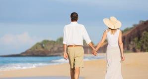 Mitt åldrades par som tycker om, går på stranden Arkivfoton