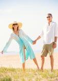 Mitt åldrades par som tycker om, går på stranden Royaltyfria Bilder