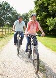 Mitt åldrades par som tycker om landscirkuleringen, rider tillsammans Arkivbilder