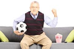 Mitt åldrades sportfanen som rymmer en fotbollboll och håller ögonen på sporten royaltyfri bild
