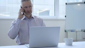 Mitt åldras affärsman Talking på telefonen som diskuterar arbete royaltyfri fotografi