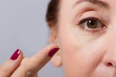 Mitt åldras kvinna som applicerar eller sätter kontaktlinsen för vision i hennes bruna öga vid fingret Slut som är övre och isole royaltyfri bild