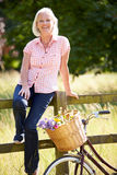 Mitt åldras kvinna som kopplar av på landscirkuleringsritt Arkivbilder