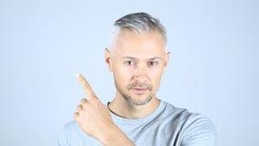 Mitt åldras man som pekar på sidan, kopieringsutrymme Fotografering för Bildbyråer