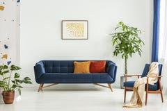 Mitt--århundrade modern stol med en filt och en stor soffa med färgrika kuddar i en rymlig vardagsruminre med grönt plan royaltyfri bild