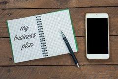 Mitt affärsplan, text på anteckningsboken, blyertspenna och ilar telefonen Arkivbild