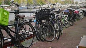 Mitt av Amsterdam - cyklar som parkerar nära amstelkanalen, Nederländerna Fotografering för Bildbyråer