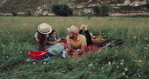 Mitt av naturen, picknicktid med en ung familj, alla medlemmar lägger ner på filten som rymmer sig stock video