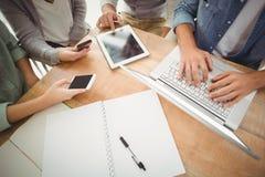 Mitt- avsnitt av affärsfolk som använder bärbara datorn och smartphones arkivfoton