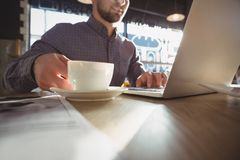 Mitt- avsnitt av affärsmannen med kaffe genom att använda bärbara datorn i kafé arkivbild