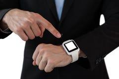 Mitt- avsnitt av affärsmannen som pekar på den smarta klockan Arkivfoto