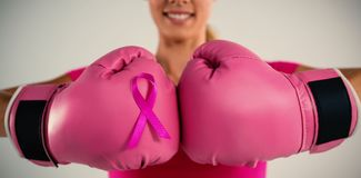 Mitt- avsnitt av att le kvinnan med boxninghandskar och det rosa bandet Royaltyfri Fotografi