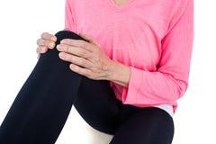 Mitt- avsnitt av den mogna kvinnan som masserar knäet Arkivbilder