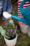Mitt- avsnitt av höga par som planterar i trädgård arkivfoto