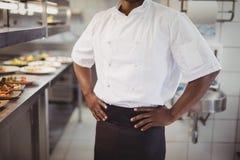 Mitt- avsnitt av kockanseendet med händer på höft i kommersiellt kök arkivfoton