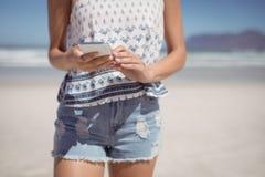 Mitt- avsnitt av kvinnan som använder mobiltelefonen på stranden royaltyfri foto