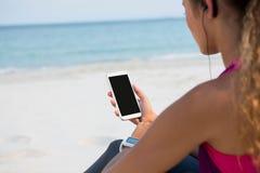 Mitt- avsnitt av kvinnan som använder mobiltelefonen på stranden arkivfoto