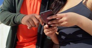Mitt- avsnitt av par genom att anv?nda mobiltelefonen p? en solig dag 4k arkivfilmer