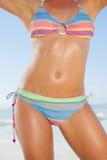 Mitt- avsnitt av passformkvinnan i bikini på stranden royaltyfri fotografi